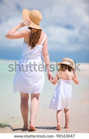 Back view of mother and daughter walking on beach