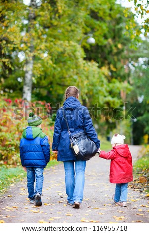 Back view of mother and kids outdoors at beautiful autumn park