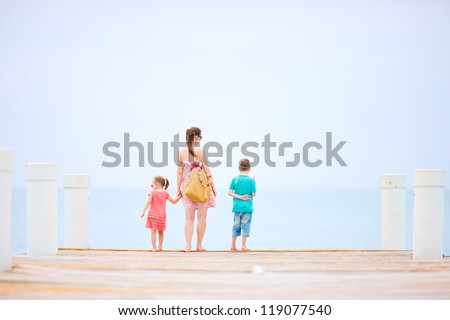 Back view of mother and kids outdoors on a wooden dock
