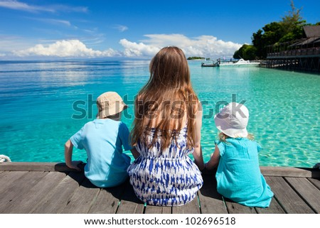 Back view of mother and kids sitting on wooden dock