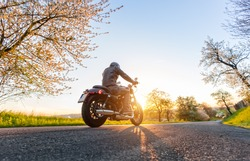 Back view of motorcycle driver driving in beautiful sunset