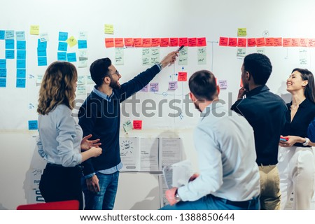 Back view of multicultural group of successful male and female partners discussing ideas for company startup project while one man pointing on information on sticks, concept of collaboration
