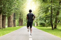 Back view of muscular black guy jogging by park path, healthy lifestyle concept, empty space