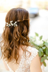 Back view of nice brown curls for bride keeping flowers. Concept of wedding photo session and stylish hair do.