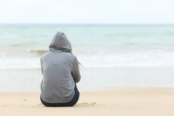Back view of one teenager girl thinking alone and watching the sea sitting on the sand of the beach with the horizon in the background