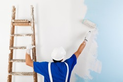Back view of  painter in white dungarees, helmet and gloves painting a wall with paint roller and wooden vintage ladder, with copy space