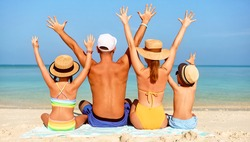 Back view of parents embracing with children all wearing swimsuits and hats while sitting on blanket and  raising arms on sandy coast enjoying ocean