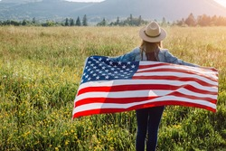 Back view of patriotic young female in beige hat holding big usa United States flag standing on background field at sunny day. Hipster girl feeling freedom, independence concept. july 4th concept