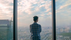 Back view of pensive woman looking at cityscape through window of skyscraper. Summer time, cloudy, daylight. Success, opportunity, sightseeing, discover and future concept