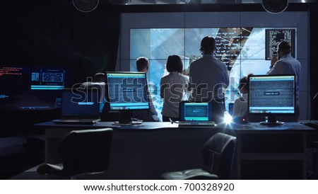 Back view of people working and managing flight in mission control center. Elements of this image furnished by NASA.
