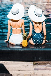 back view of pin up girls in swimsuits and hats sitting with pineapple at swimming pool