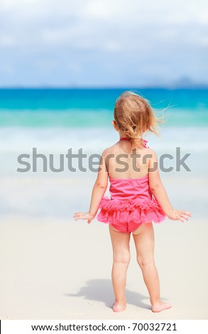 Back view of playful toddler girl on white sand beach