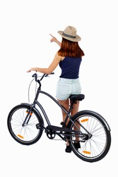 back view of pointing woman with a bicycle. cyclist sits on the bike. Rear view people collection.  backside view of person. Isolated over white background. Girl cyclist is leaning on a bicycle.