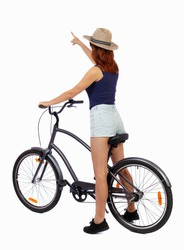 back view of pointing woman with a bicycle. cyclist sits on the bike. Rear view people collection.  backside view of person. Girl in a straw hat shows his hand forward while sitting on the bike.