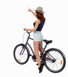 back view of pointing woman with bicycle. cyclist sits on bike. Rear view people collection. backside view person. Isolated over white background. Girl in a straw hat shows his hand forward with bike