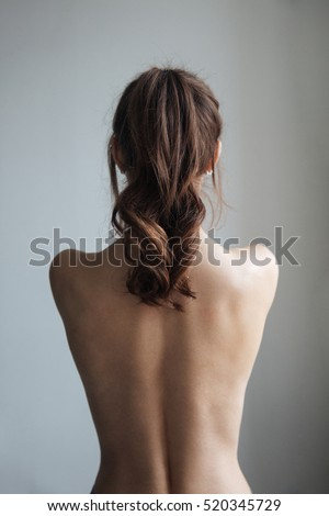 Back view of pretty naked woman. isolated gray background