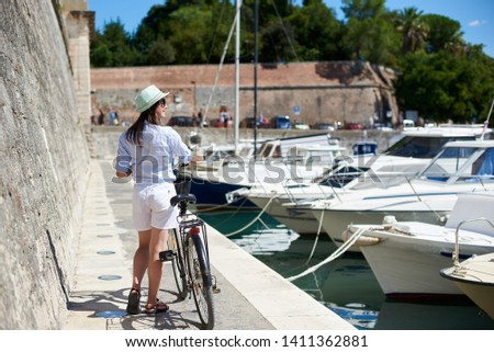 Back view of pretty smiling young woman in sunglasses and hat standing with bicycle on stone path along the sea by high stone defensive wall and long row of tied boats. Active lifestyle concept. #1411362881