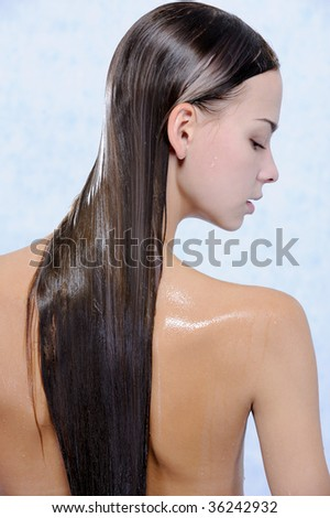 Back view of pretty young female with wet long hairs