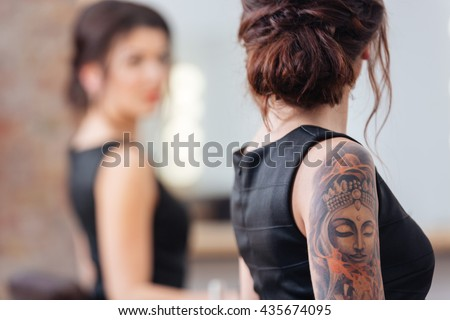 Back view of pretty young woman in black dress with tattoo on her hand standing in front of the mirror