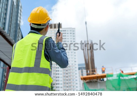 back view of professional engineer asian male safety helmet manage control constuction site with expertise working #1492840478