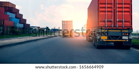 Back view of Red Container truck in ship port Logistics.Transportation industry in port business concept.import,export logistic industrial Transporting Land transport on Port transportation storge