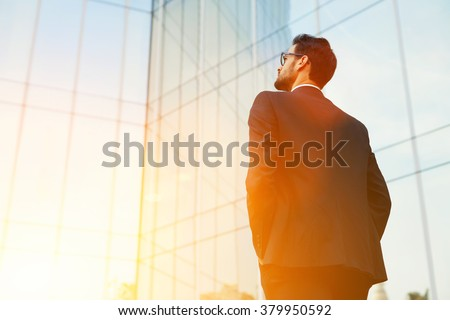 Back view of rich businessman with hands in pockets looking on his skyscraper building while standing outside, young confident male manager dreaming about growth his career during work break outdoors