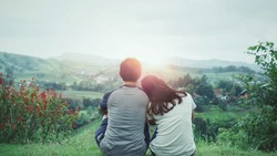Back view of Romantic Couple in love sitting on grass field and watch the mountain landscape in sunrise morning.  Couple love dating in holiday trip concept.