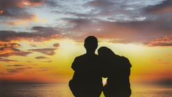 Back view of romantic Couple lovers silhouetted sitting together on beach and looking at sunset cloudy sky.