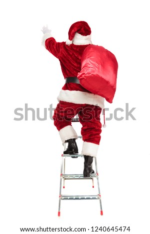 back view of santa stretching hand while climbing the ladder and standing on white background, ful length picture