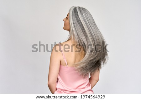 Back view of senior mature middle aged older Asian lady with long gray natural coloring vibrant silky hair. Dry hair replenishing healing treatment for women after menopause advertising concept.