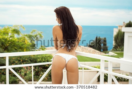 Back view of sexy model in bikini posing in summer scenery #370518482