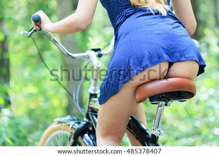back view of sexy young woman sitting on the bike outdoors
