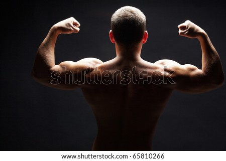 Back view of shirtless man demonstrating his strong arms