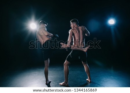 back view of shirtless mma fighter kicking another sportsman during muay thai training