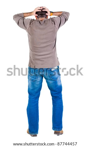 Back view of shocked and scared young  man. Holds hands upwards. Rear view. Isolated over white background.