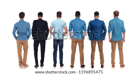back view of six relaxed young men wearing suits and blue shirts standing on white background with hands in pockets, full length picture