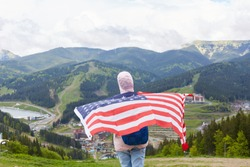 Back view of slender active tourist being fond of leisure activities, go hiking, holding U.S. flag, covering her back with it, looking at mountains and holiday resort, splendid view of nature around.