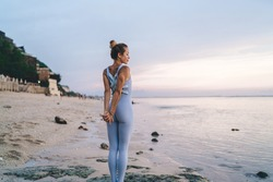 Back view of slim athletic female in sportswear stretching muscles of back and arms holding hands in wrist lock grip behind back while relaxing at seashore near water in Bali
