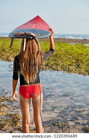 Back view of slim woman in red bikini, has long hair, keeps surfboard over head, being fastened by leash for protection, admires ocean landscape, has active lifestyle, involved in exteme water sport