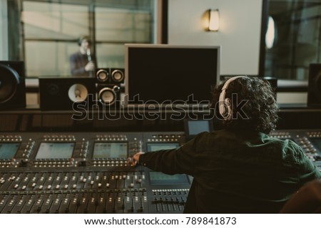 back view of sound producer working at studio while recording song #789841873