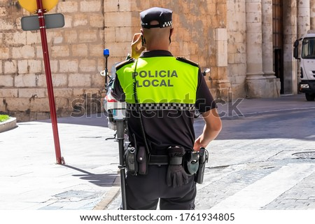 Back view of Spanish municipal police  with 'Policia Local' logo emblem on uniform maintain public order in the streets of Jaen, Spain Foto stock ©