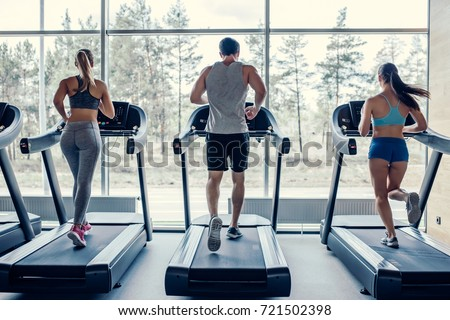Back view of sports people on running track. Two attractive young women and handsome muscular man are running in gym. Treadmills.