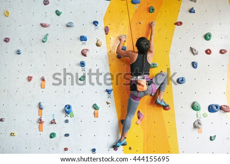 Back view of sportswoman climbing in the gym #444155695