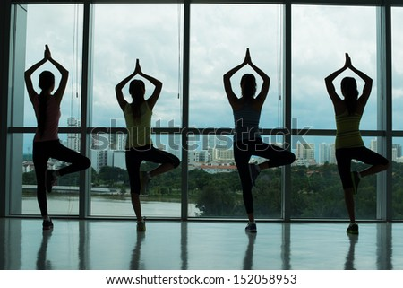 Back view of sportswomen standing in yoga position