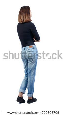 back view of standing young beautiful  woman.  girl  watching. Rear view people collection.  backside view of person. girl in jeans and a black T-shirt is standing sideways with her hands on her chest