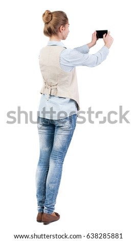 back view of standing young beautiful  woman  in vest and using a mobile phone. girl  watching. Isolated over white background. Girl doing selfie on your phone.