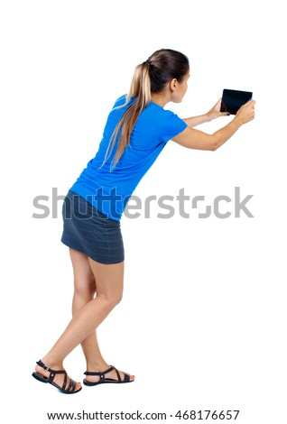 back view of standing young beautiful  woman  using a mobile phone. girl  watching. Rear view people collection.  backside view of person.  Isolated over white background. girl in a short skirt and a