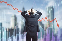 Back view of stressed young businessman looking at downward red arrow on blurry city background. Decrease, investment and economy concept. Multiexposure