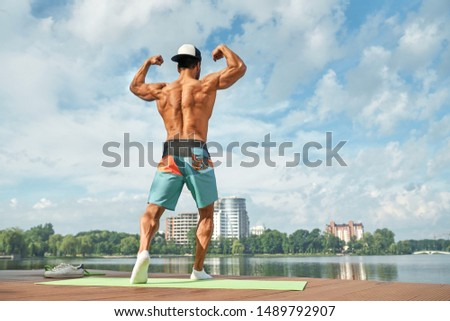 Back view of stronger male with bare chest and perfect sunburn posing outdoors, showing his shoulder and back muscles. Athletic male in pose using biceps and triceps. Beautiful place with wooden pier.
