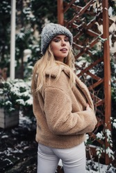 Back view of stylish female in warm outerwear standing in snow covered park and looking over shoulder at camera in winter day
